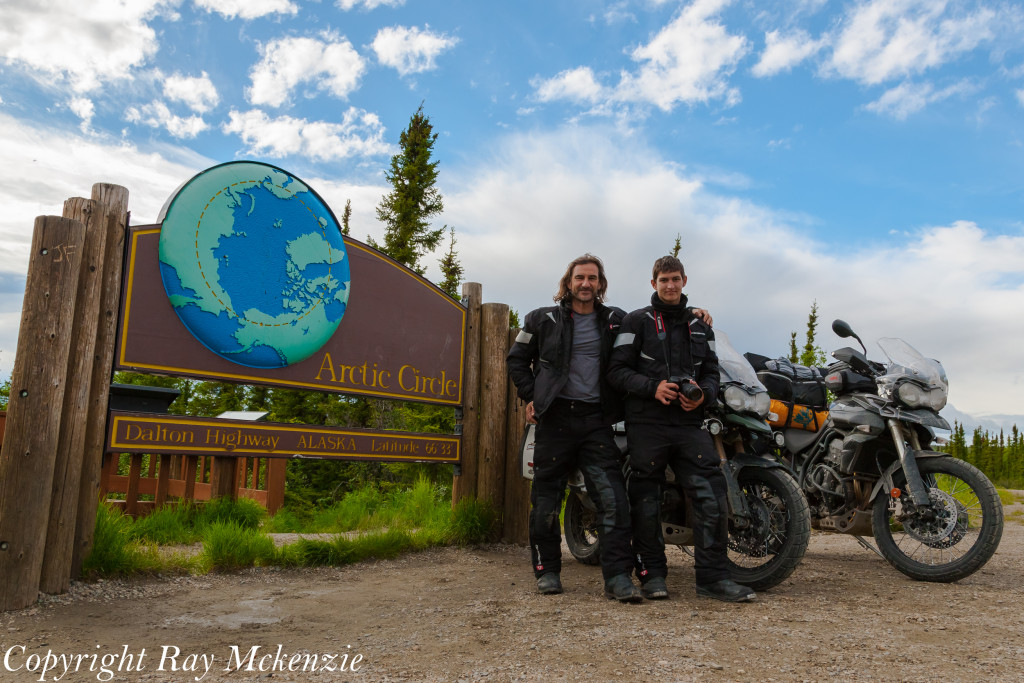 Neale Bayly with Ray Mckenzie Alaska Adventure on Triumph Motorcycles Arctic Circle Sign